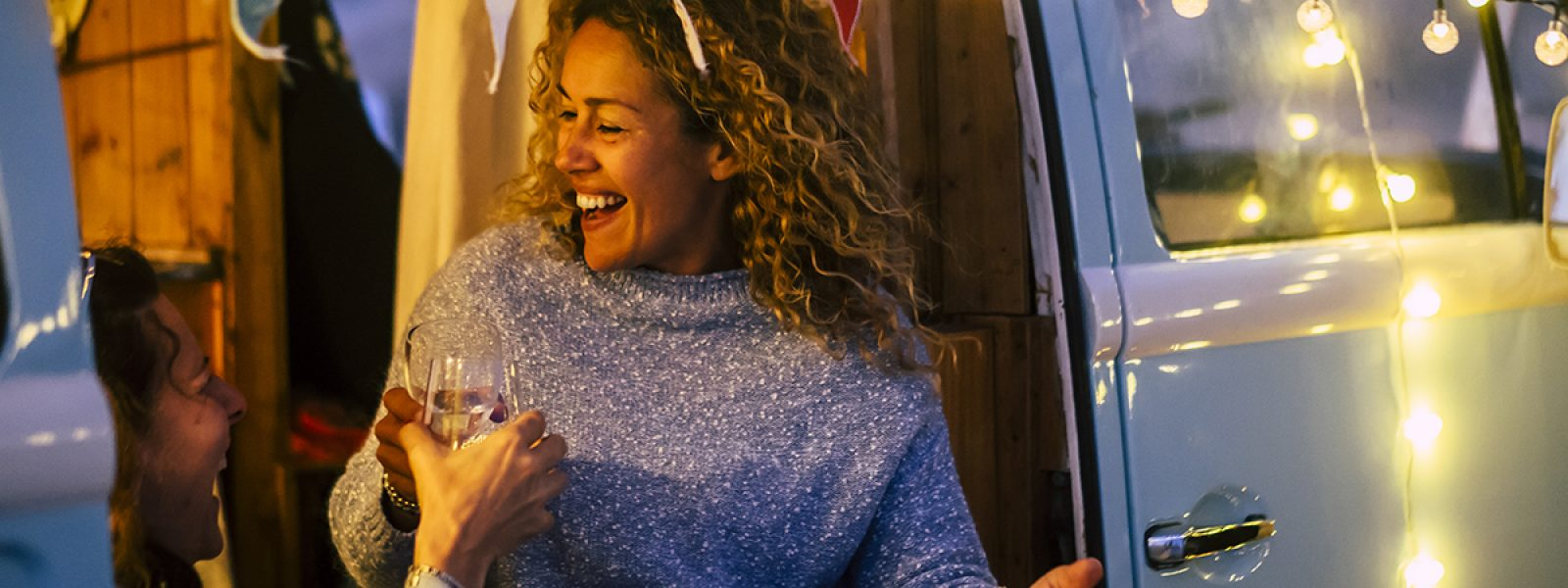 Alternative travel and celebration concept with couple of people adult cheerful happy women celebrate together in a vintage van camper  and party lights outdoor